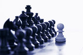 White pawn challenging black chess pieces — Stock Photo