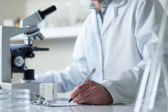 Scientist conducting research with microscope selective focus — Stock Photo