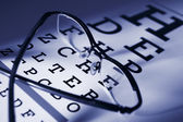 Glasses and eytest chart differential focus blue tone — Foto Stock