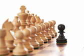 Black pawn challenging army of white chess pieces — Stock Photo