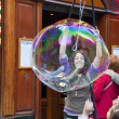 Постер, плакат: Girl making huge soap bubbles