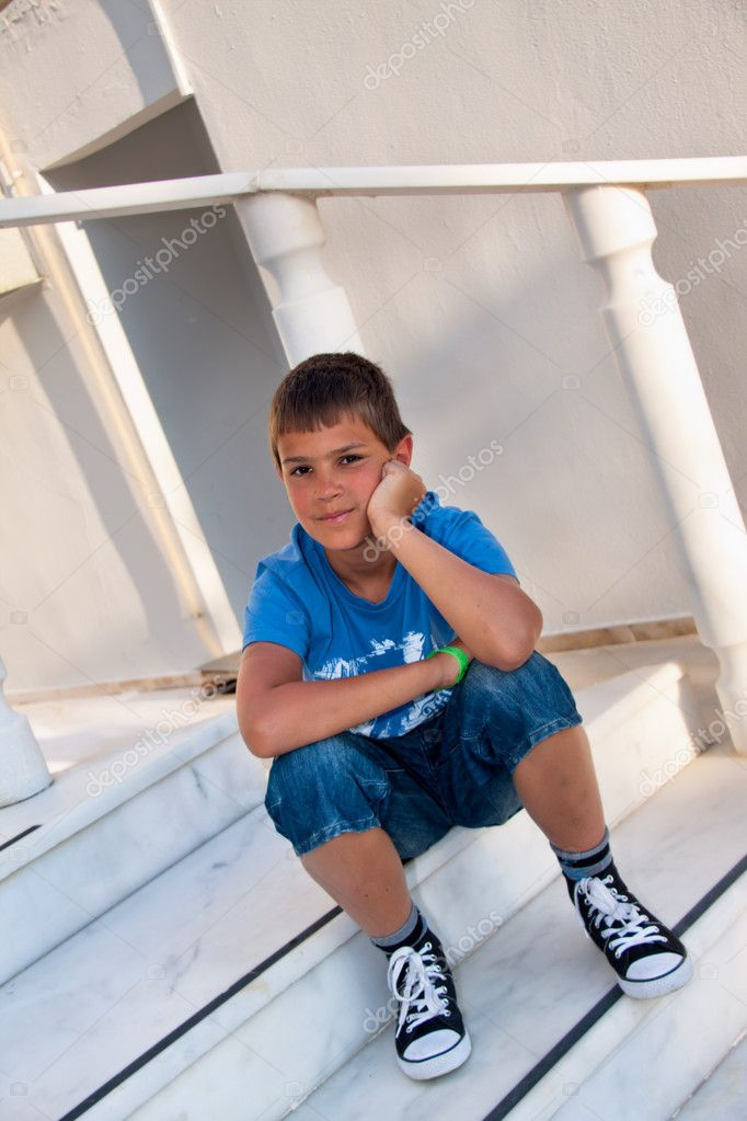 The carefree boy dreams sitting on a porch — Stock Photo #10071288