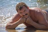 The man sunbathes on sand — Stock Photo
