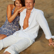 Beautiful couple having rest on river beach — Stock Photo
