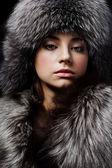 Beautiful young girl in fur clothes. Studio shot — Stock Photo