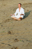 Beautiful man meditating on river beach — Stock Photo