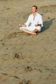 Beautiful man meditating on river beach — Stock Photo