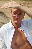 Beautiful man having rest on river beach. Outdoor shot — Stock Photo