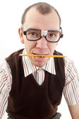 Nerdy guy biting pencil — Zdjęcie stockowe