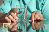 Hands of old woman with a pill and water — Stock Photo
