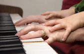 Hands of piano player and the child — Stock Photo