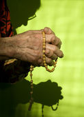 Hands of old woman by prayer of rosary — Stock Photo
