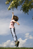 Jump of little girl and tree in the spring — Stock Photo