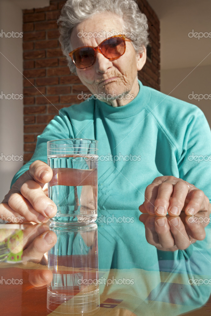 Glass of water and old woman — Stock Photo #10219003
