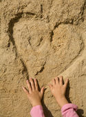 Heart in the sand and hand of the child — Stock Photo