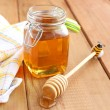 Jar of honey and wooden drizzler — Stock Photo