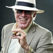 Senior gangster man smoking cigar wearing light suit and hat with vintage sunglasses. — Stock Photo