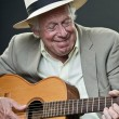 Senior jazz musician with accoustic guitar wearing suit and hat. — Stock Photo