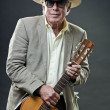 Stock Photo: Senior man with accoustic guitar wearing suit hat and sunglasses.