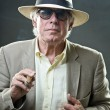 Senior man with hat and sunglasses smoking cigar. — Stockfoto