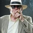 Royalty-Free Stock Photo: Senior man with hat and sunglasses smoking cigar.