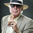Senior man with hat and sunglasses smoking cigar. — Stock Photo