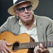 Senior man with hat and sunglasses playing accoustic guitar. — Stock Photo