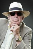 Senior man in suit wearing hat and sunglasses isolated on grey background. — Stock Photo