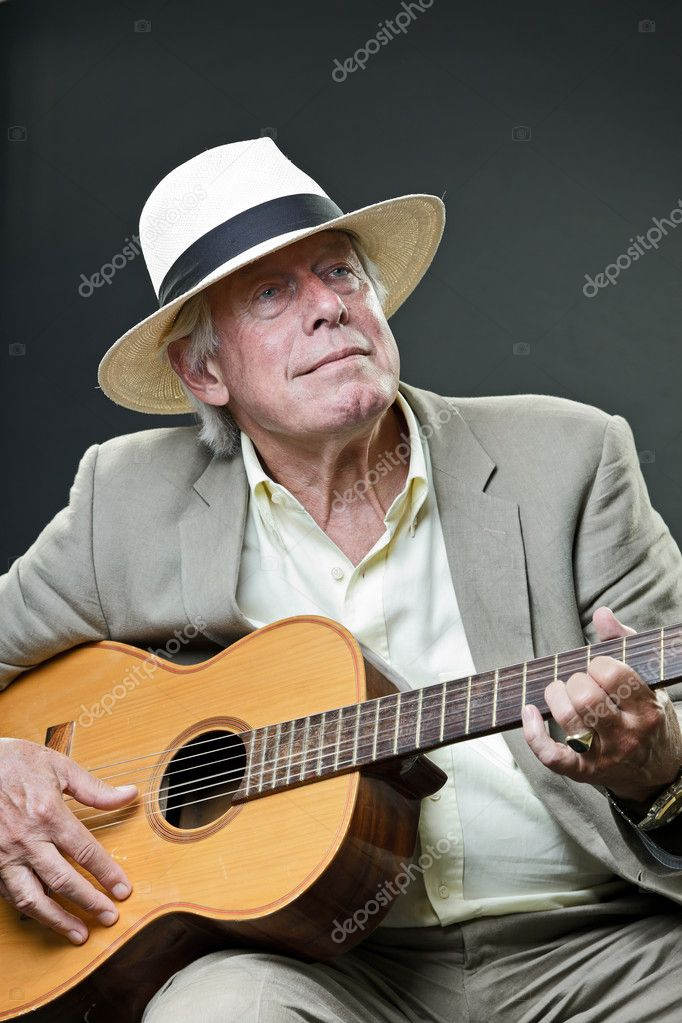 Studio portrait of senior man with hat sunglasses and guitar. Jazz musician. Isolated on grey background.  Stock Photo #10163355