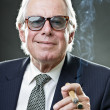 Senior business man smoking cigar wearing vintage sunglasses and blue suit with tie. — Stock Photo