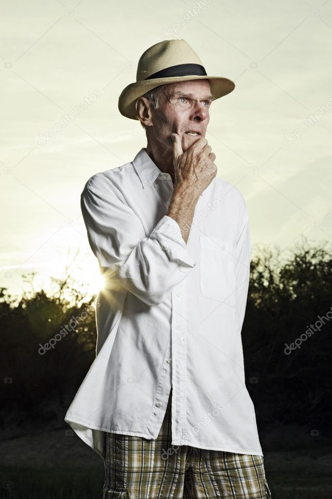 Good looking senior man enjoying the freedom of nature on beautiful sunny day. Sportive healthy and in good shape. Landscape of dunes with blue cloudy sky. Sunset at dusk. End of the day. Playing with water. — Stock Photo #10217618
