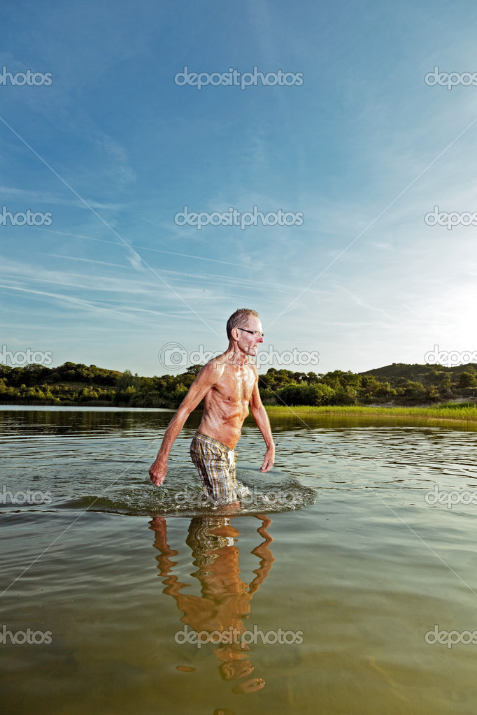 Good looking senior man enjoying the freedom of nature on beautiful sunny day. Sportive healthy and in good shape. Landscape of dunes with blue cloudy sky. Sunset at dusk. End of the day. — Stock Photo #10218482
