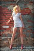 Beautiful blond girl beside brick wall — Stockfoto