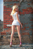 Beautiful blond girl beside brick wall — Photo