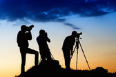 Three man silhouetes photographing the sky — Stock Photo