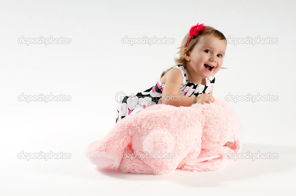 A little girl playing with a pink bunny toy — Stock Photo #10118823
