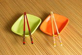 Two coloured sauce-boats with chopsticks — Stock Photo