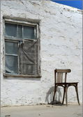 Old chair on a background an old house — Stockfoto