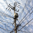 Chaotic tangle of wires on transmission pole — Stock Photo #10711085