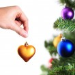 Hand decorating christmas tree with golden heart — Stock Photo #10711849