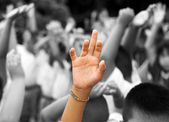 Hand raised among others hands in background — Stock Photo