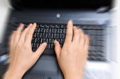 Zoomed in view of female hands typing on computer — Stock Photo