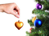 Hand decorating christmas tree with golden heart — Stock Photo