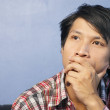 Stock Photo: Young Asian Man Thinking