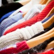 Rack of jumpers at market, close-up - Stock Photo