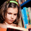 Young girl reading in library — Foto de stock #10376205