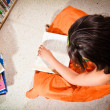 Young girl reading in library — Photo