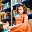 Young girl reading in library — Foto de stock #10376258