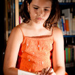 Young girl reading in library — Stockfoto #10376293