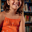 Stock Photo: Young girl laughing in library